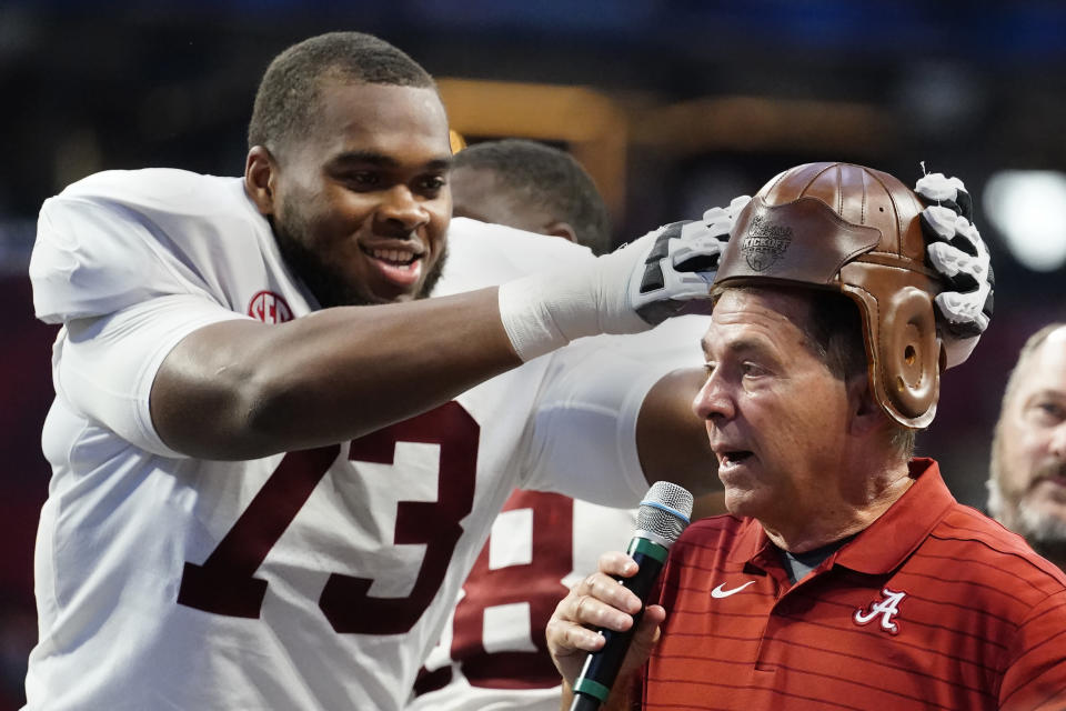"""Alabama offensive lineman Evan Neal (73) places the leather helmet from the """"Old Leather Helmet Torphy"""" on head coach Nick Saban's head after they defeated Miami in the Chick-fil-A Kickoff NCAA college football game Saturday, Sept. 4, 2021, in Atlanta. (AP Photo/John Bazemore)"""