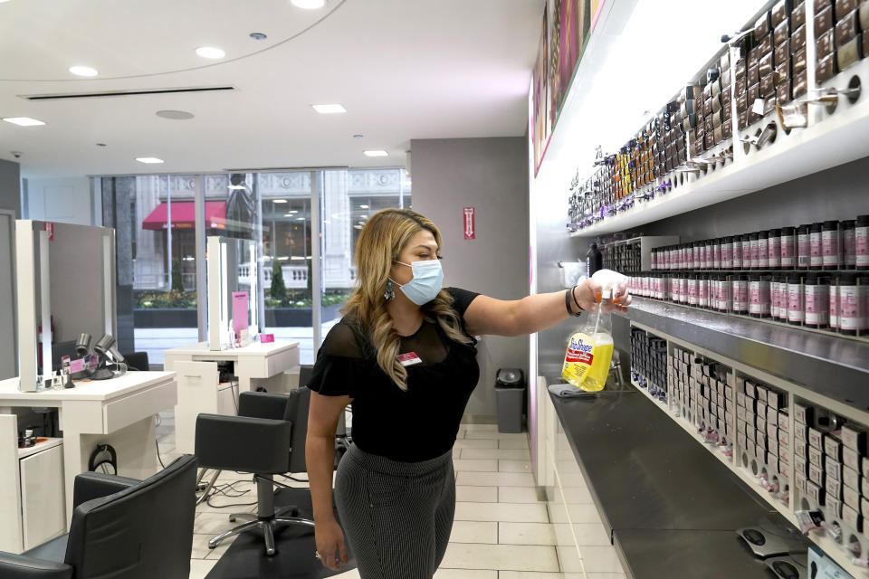 Teena Sutton sanitizes a shelve Thursday, Nov. 19, 2020, at an Ulta beauty store on Chicago's Magnificent Mile. (AP Photo/Charles Rex Arbogast)