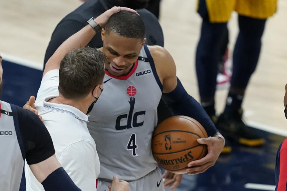 Washington Wizards head coach Scott Brooks talks with Russell Westbrook following an NBA basketball game against the Indiana Pacers, Saturday, May 8, 2021, in Indianapolis. Washington won 133-132 in overtime. (AP Photo/Darron Cummings)