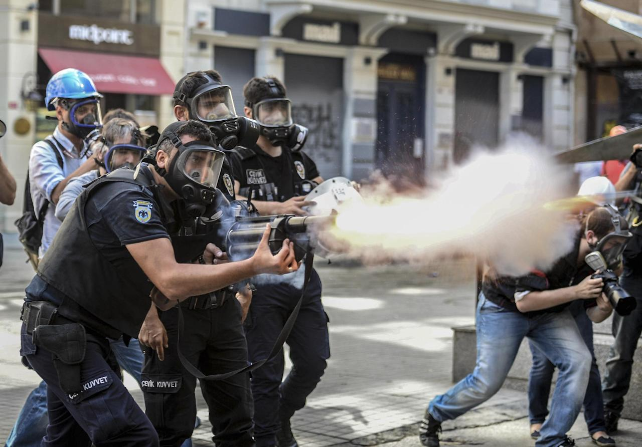 Police fire tear gas as riot police spray a water canon at demonstrators who remained defiant after authorities evicted activists from an Istanbul park, making clear they are taking a hardline stand against attempts to rekindle protests that have shaken the country, near city's main Taksim Square in Istanbul, Turkey, Sunday, June 16, 2013. (AP Photo )