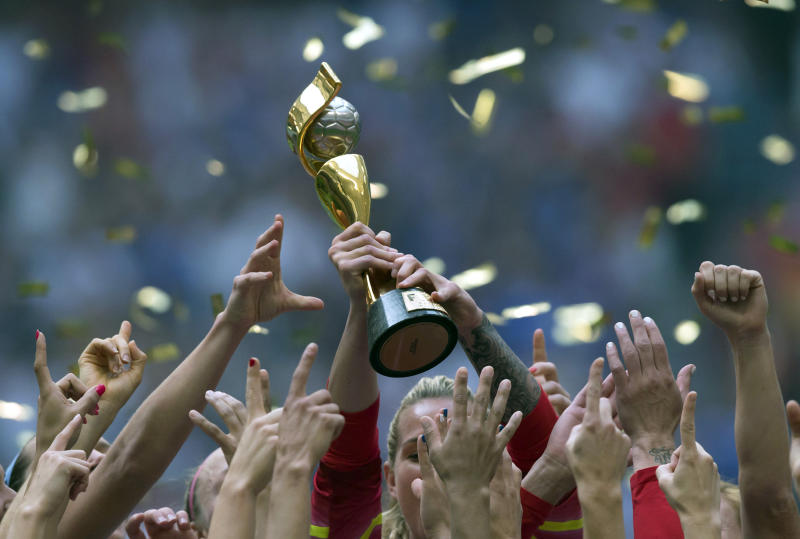 FILE - In this July 5, 2015, file photo, the United States Women's National Team celebrates with the trophy after they defeated Japan 5-2 in the FIFA Women's World Cup soccer championship in Vancouver, British Columbia, Canada. People with knowledge of FIFA's finances told The Associated Press that in the four-year period covering the 2018 World Cup, FIFA's reserves soared to $2.74 billion and revenue rose to $6.4 billion, but it also underscores the glaring disparity between men and women's soccer. (Darryl Dyck/The Canadian Press via AP, File)