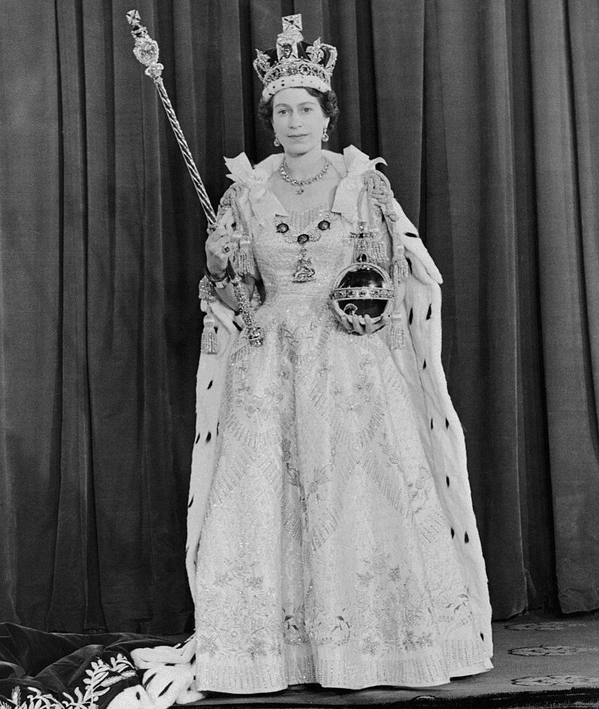 Queen Elizabeth in a gown, a fur coat, and a crown