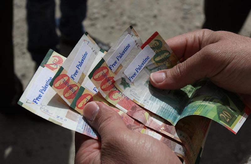 "A Palestinian man holds new Israeli Shekels' bills marked with stickers reading ""Free Palestine"" on March 7, 2011 in the West Bank city of Ramallah (AFP Photo/Abbas Momani)"