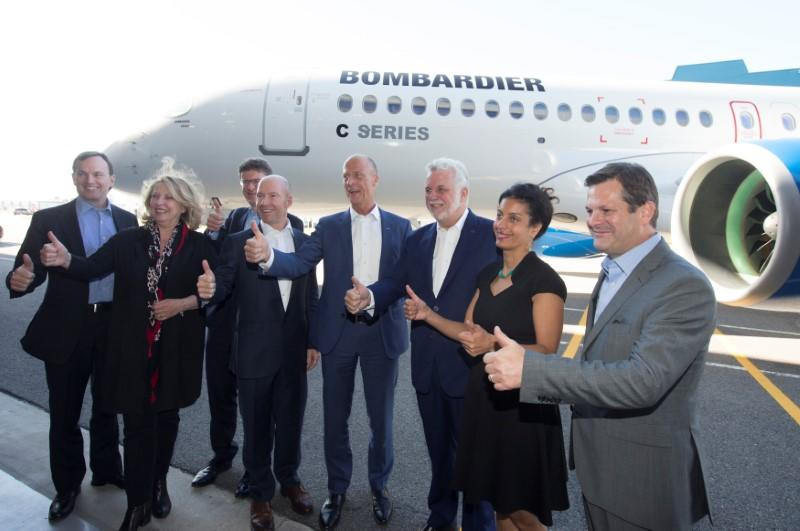 Bombardier, Airbus and other dignitaries give thumbs up in front of C Series plane at Bombardier's plant in Mirabel