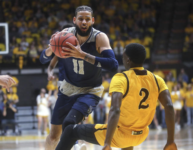 Nevada forward Cody Martin (11) charges forward past Wyoming forward AJ Banks during the first half of an NCAA college basketball game, Saturday, Feb. 16, 2019, in Laramie, Wyo. (AP Photo/Jacob Byk)