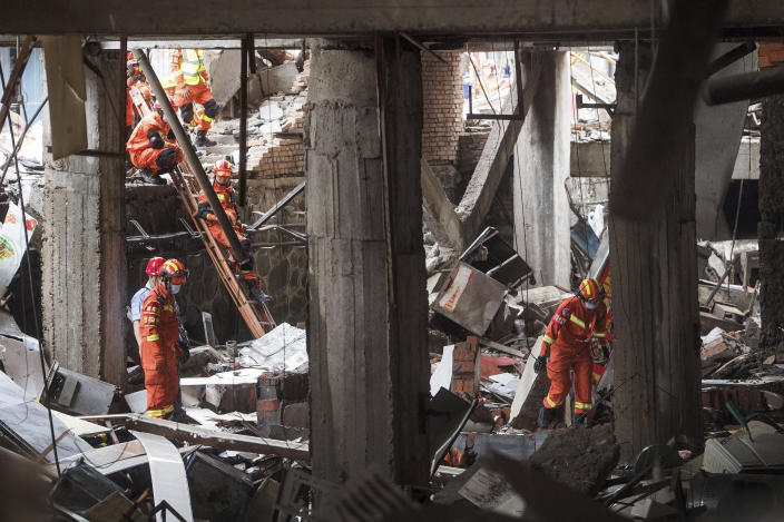 In this photo released by Xinhua News Agency, rescue workers search for survivors in the aftermath of a gas explosion in Shiyan city in central China's Hubei Province on Sunday, June 13, 2021. At least a dozen people were killed and more seriously injured Sunday after a gas line explosion tore through the residential neighborhood in central China. (Xiao Yijiu/Xinhua via AP)