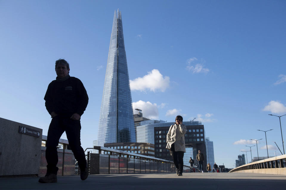 People cross London Bridge backdropped by the Shard skyscraper as workers return to offices following the Easter holiday, in London, Tuesday April 6, 2021.  Virus lockdown restrictions are eased in England to allow far greater freedom outdoors. (Dominic Lipinski/PA via AP)