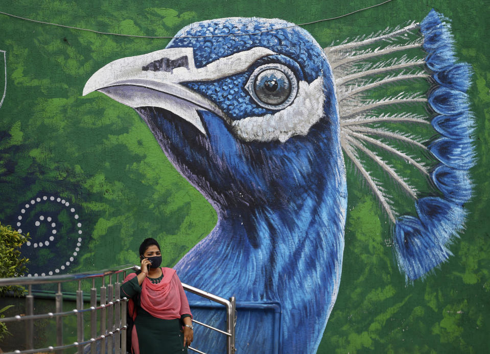 An Indian woman wearing face mask as a precaution against the coronavirus speaks on mobile phone standing in front of a Peacock graffiti on a wall in Hyderabad, India, Thursday, June 17, 2021. (AP Photo/Mahesh Kumar A.)