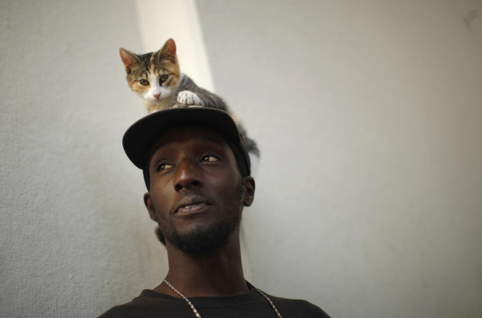Michael Norton, 23, who does not have health insurance, stands with his cat M.J. at a Covered California event which marks the opening of the state's Affordable Healthcare Act, commonly known as Obamacare, health insurance marketplace in Los Angeles, California, October 1, 2013. Technical glitches and heavy internet traffic slowed Tuesday's launch of new online insurance exchanges at the heart of President Barack Obama's healthcare reform, showcasing the challenge of covering millions of uninsured Americans. REUTERS/Lucy Nicholson (UNITED STATES - Tags: ANIMALS POLITICS HEALTH)