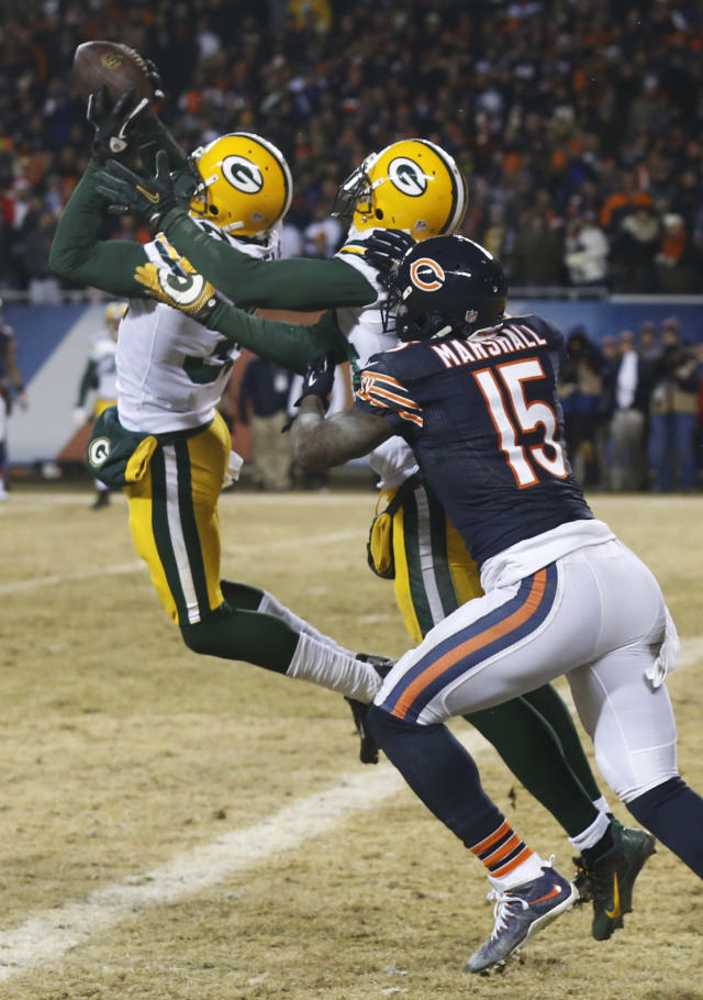 Green Bay Packers cornerback Sam Shields, left, intercepts a pass intended for Chicago Bears wide receiver Brandon Marshall (15) to end the game during the second half of an NFL football game, Sunday, Dec. 29, 2013, in Chicago. The Packers won 33-28 to capture the NFC North title. (AP Photo/Charles Rex Arbogast)