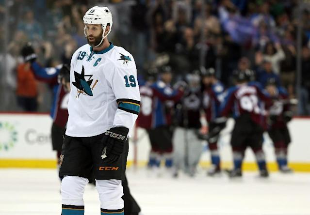 San Jose Sharks center Joe Thornton heads off ice as members of the Colorado Avalanche celebrate in the background after the Avalanche's 3-2 victory in an NHL hockey game in Denver on Saturday, March 29, 2014. (AP Photo/David Zalubowski)