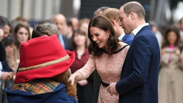 Britain's Catherine, Duchess of Cambridge shakes hands with a person in a Paddington Bear outfit along with her husband Britain's Prince William, Duke of Cambridge, as they attend a charities event at Paddington train station in London, Oct. 16, 2017. (Chris J Ratcliffe/AFP/Getty Images)