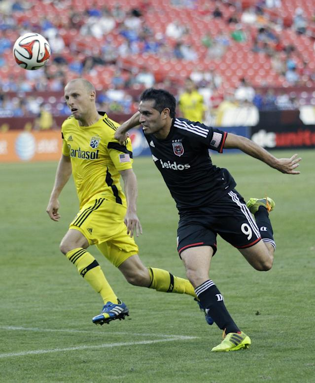 D.C. United's Fabian Espindola (9) and Columbus Crew's Eric Gehrig, left, chase the ball during the second half of an MLS soccer game, Saturday, June 7, 2014, in Landover, Md. The game ended in a scoreless tie. (AP Photo/Luis M. Alvarez)