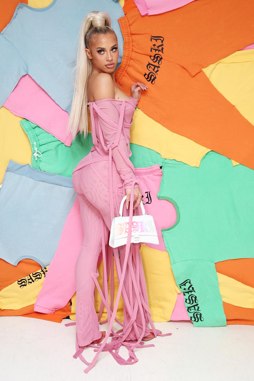 Tammy Hembrow poses in a pink outfit at the Saski Collection event during Afterpay Australian Fashion Week 2021 '22 Collections at Meu Jardim Sydney on June 03, 2021 in Sydney, Australia