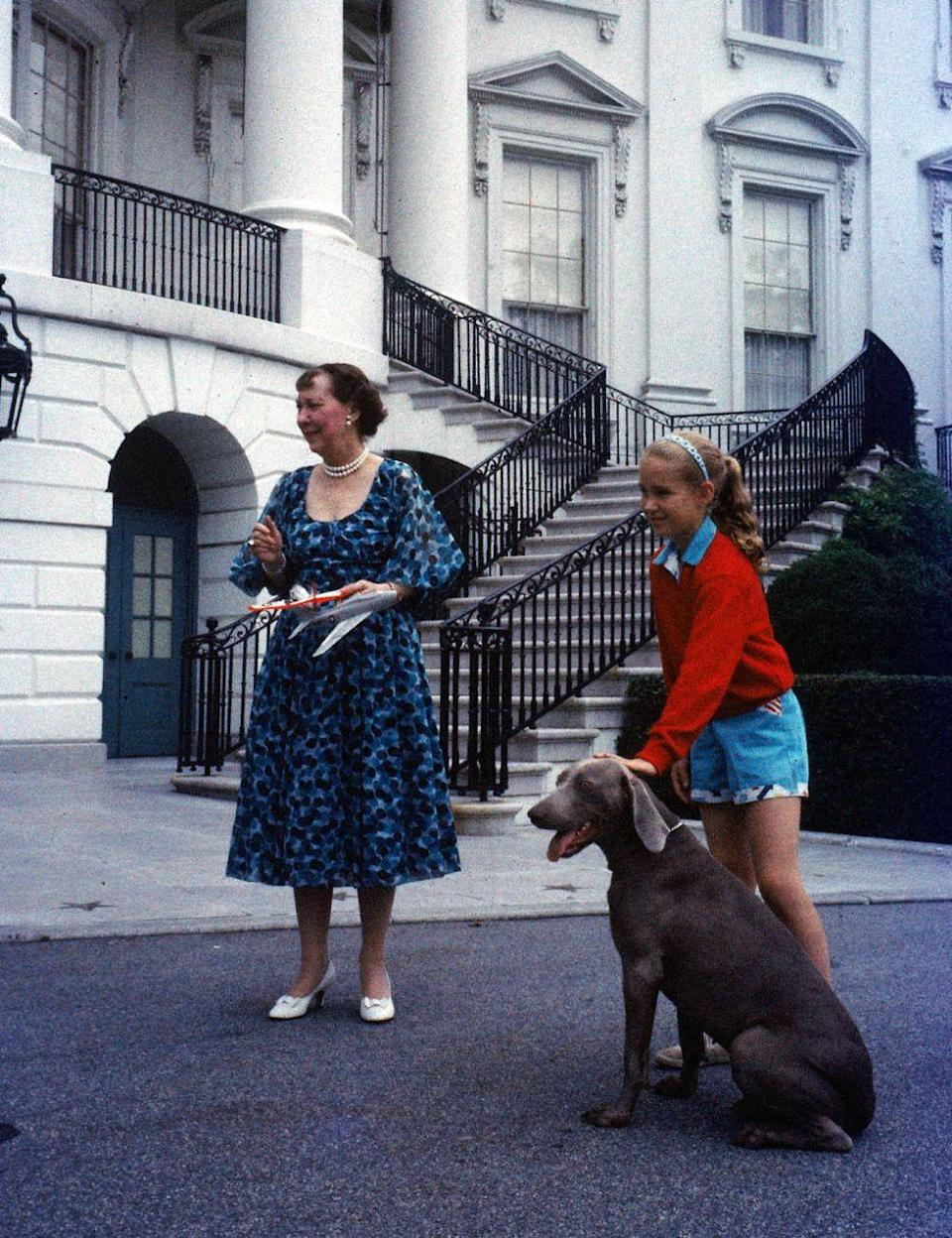 <p>First Lady Mamie Eisenhower stands outside the White House with her granddaughter Barbara Anne and the Eisenhower's pet weimaraner Heidi.</p>