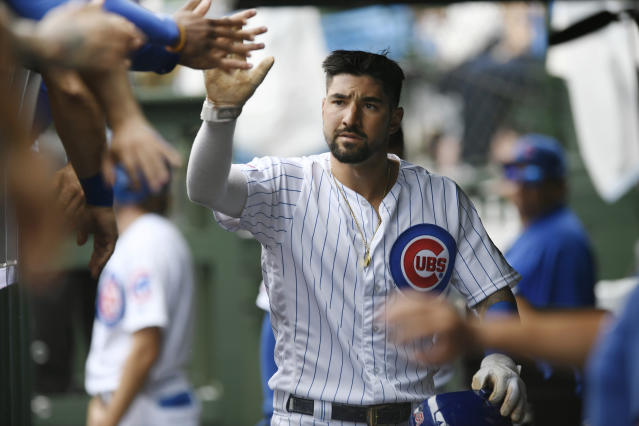 Chicago Cubs' Nicholas Castellanos celebrates with teammates in the dugout after scoring on a passed ball by St. Louis Cardinals catcher Yadier Molina during the first inning of a baseball game Sunday, Sept. 22, 2019, in Chicago. (AP Photo/Paul Beaty)