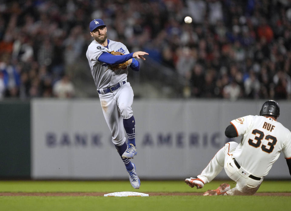 Los Angeles Dodgers shortstop Chris Taylor, left, completes a double play after forcing out San Francisco Giants' Darin Ruf (33) out on a ball hit by Jason Vosler during the fifth inning of a baseball game Wednesday, July 28, 2021, in San Francisco. (AP Photo/Tony Avelar)