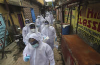 Health workers arrive to administer a free medical checkup in a slum in Mumbai, India, Sunday, June 28, 2020. India is the fourth hardest-hit country by the COVID-19 pandemic in the world after the U.S., Russia and Brazil. (AP Photo/Rafiq Maqbool)