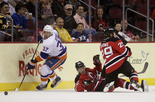 New Jersey Devils left wing Ryane Clowe (29) collides with teammate defenseman Eric Gelinas, center, as New York Islanders defenseman Brian Strait (37) skates with the puck during the first period of an NHL preseason hockey game, Thursday, Oct. 2, 2014, in Newark, N.J. (AP Photo/Julio Cortez)