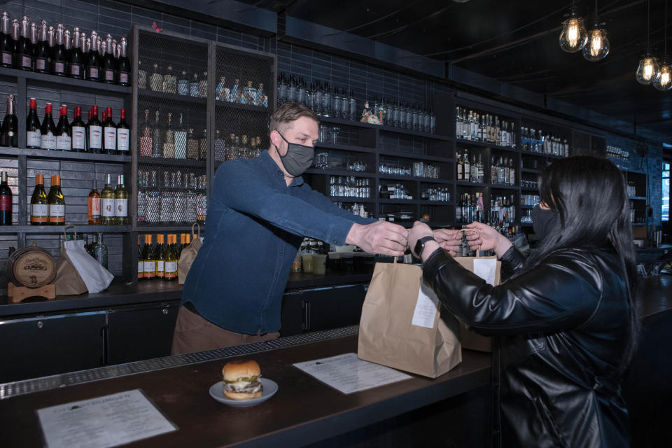 Josh Phillips, the co-owner of Espita, a stylish Mexican restaurant, hands over carryout to a customer at his restaurant in downtown Washington, Monday, Feb. 15, 2021. Phillips opened a delivery-only brand called Ghostburger in August to keep Espita's kitchen running through the winter. He chose burgers because he wanted to reach new customers at a lower price point than Espita. It's been so successful that Phillips is now scouting for locations for standalone Ghostburger restaurants. (AP Photo/Jose Luis Magana)