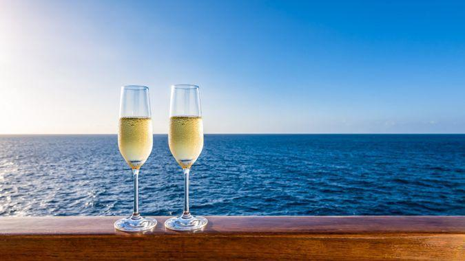 Side view of two glasses of sparkling wine on a wooden railing of a cruise ship.