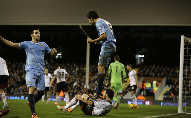 Manchester City's Jesus Navas, center, jumps as he celebrates scoring during the English Premier League soccer match between Fulham and Manchester City at Craven Cottage stadium in London, Saturday, Dec. 21, 2013. (AP Photo/Matt Dunham)