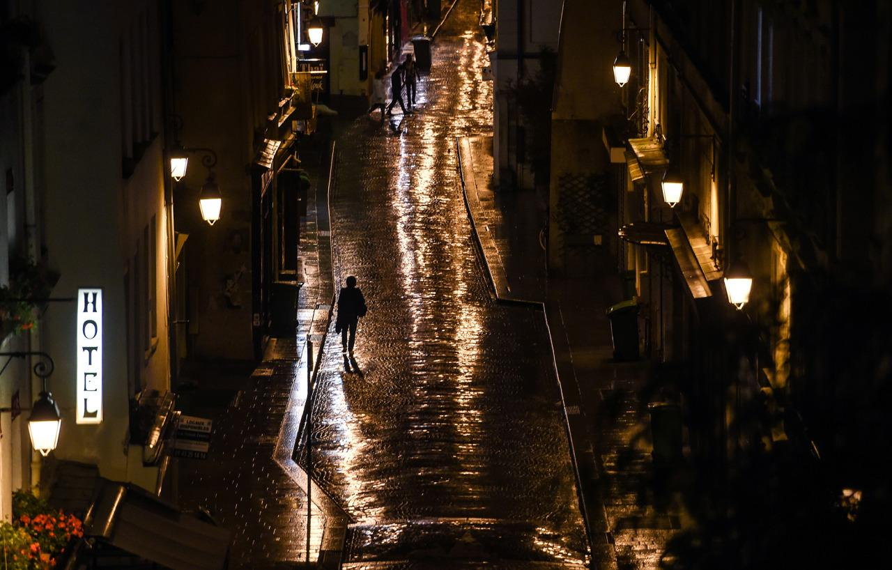 <p>Pedestrians walk on an empty street with the street lights being reflected in the wet paving following a rainy morning in the 2nd arrondissement of Paris, France, June 15, 2016. (EPA/FILIP SINGER) </p>