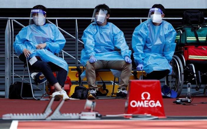 Medical officers wearing PPE at the Olympic Stadium in Tokyo - Reuters