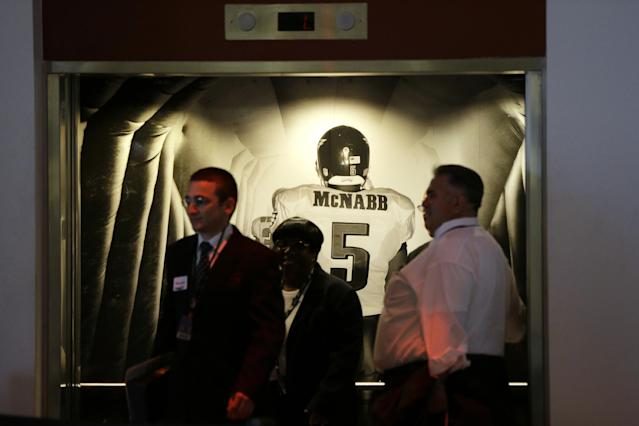 People exit an elevator past a photo mural of former Philadelphia Eagles quarterback Donovan McNabb before the Eagles' NFL football game against the Kansas City Chiefs, Thursday, Sept. 19, 2013, in Philadelphia. McNabb is scheduled to have his jersey retired at halftime. (AP Photo/Matt Rourke)