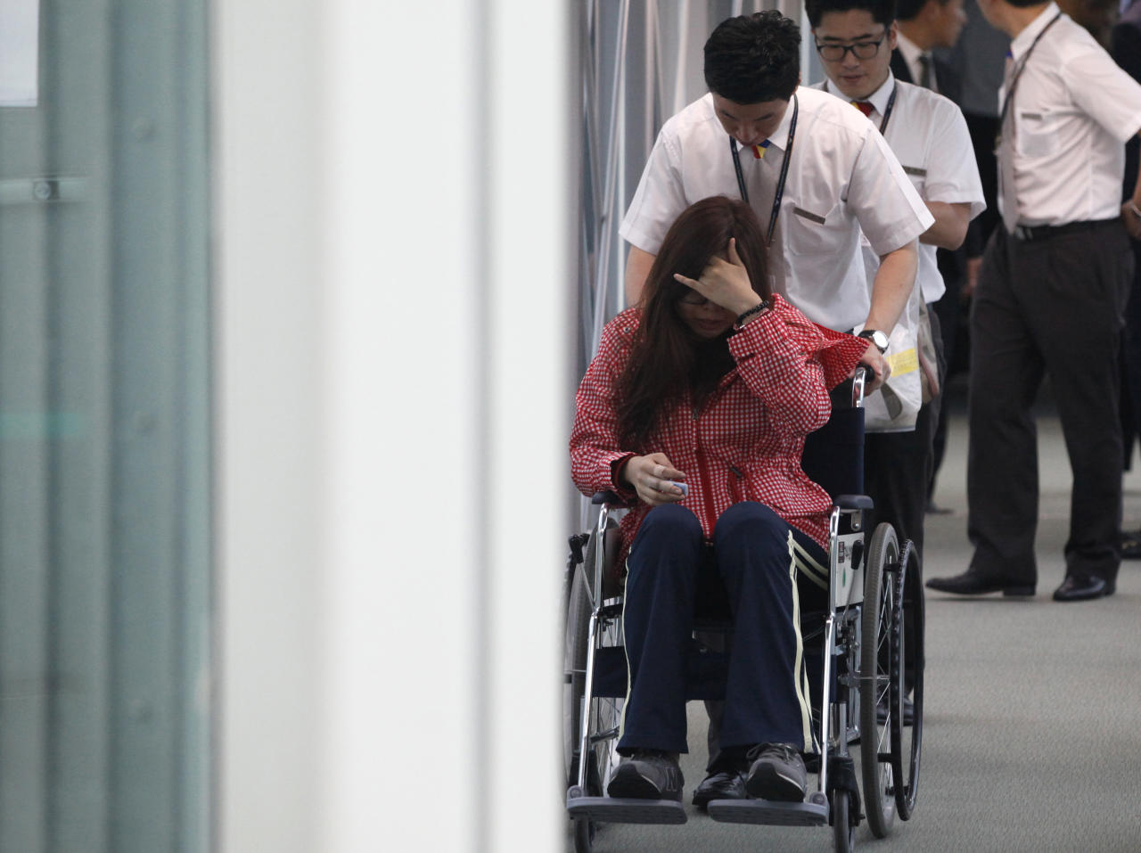 """A passenger of Asiana flight 214 arrives at the Incheon Airport in Incheon, west of Seoul Monday, July 8, 2013. Officials investigating a jetliner crash in San Francisco have determined that Asiana Airlines Flight 214 was traveling """"significantly below"""" its target speed as it approached the airport and that the crew tried to abort the landing just before it smashed onto the runway. (AP Photo/Kim Hong-Ji, Pool)"""