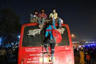 People climb on the roof of one bus at a station in New Delhi in a desperate attempt to get to their hometowns