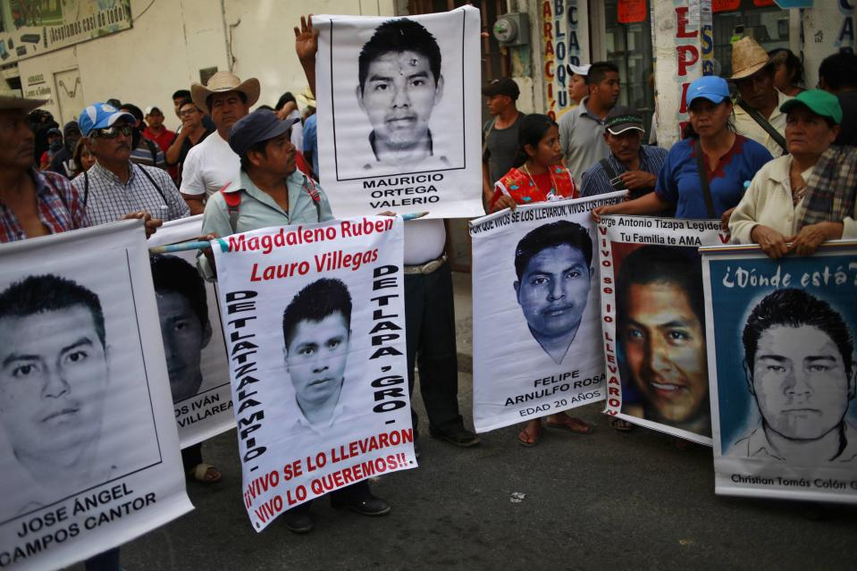 Relatives hold up posters of the 43 missing students of the Ayotzinapa Teacher Training College during a protest outside the federal court in Chilpancingo, in the Mexican state of Guerrero, January 19, 2015. The protest was held to urge the federal court to bring charges of enforced disappearance and murder against the former mayor of Iguala, Jose Luis Abarca, and his wife Maria de los Angeles Pineda Villa, for the massacre of the missing students in September 2014. REUTERS/Jorge Dan Lopez (MEXICO - Tags: CRIME LAW EDUCATION POLITICS CIVIL UNREST)
