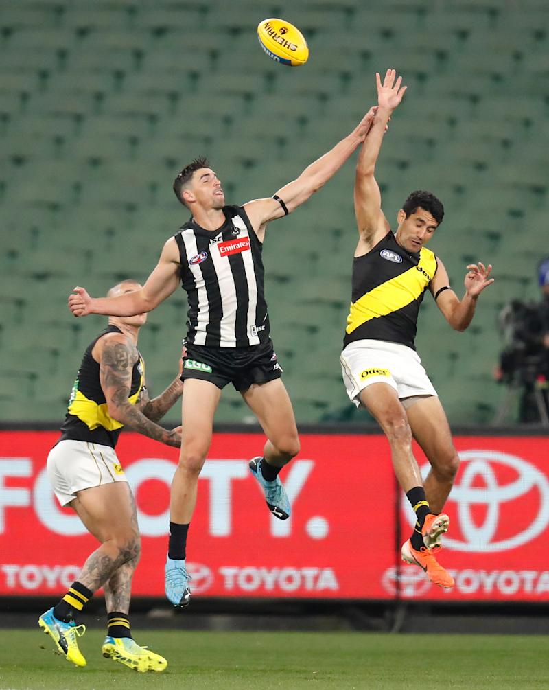 Scott Pendlebury (pictured left) and Marlion Pickett (pictured right) jump for the ball.