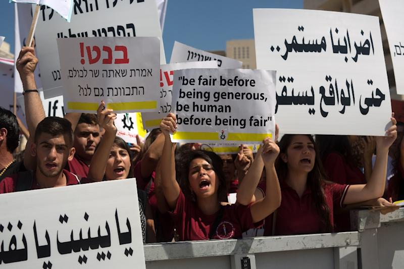 Arab Israeli Christian students hold signs during a protest to demand more funds for Christian schools, outside the Israeli Prime Minister's office in Jerusalem, September 6, 2015