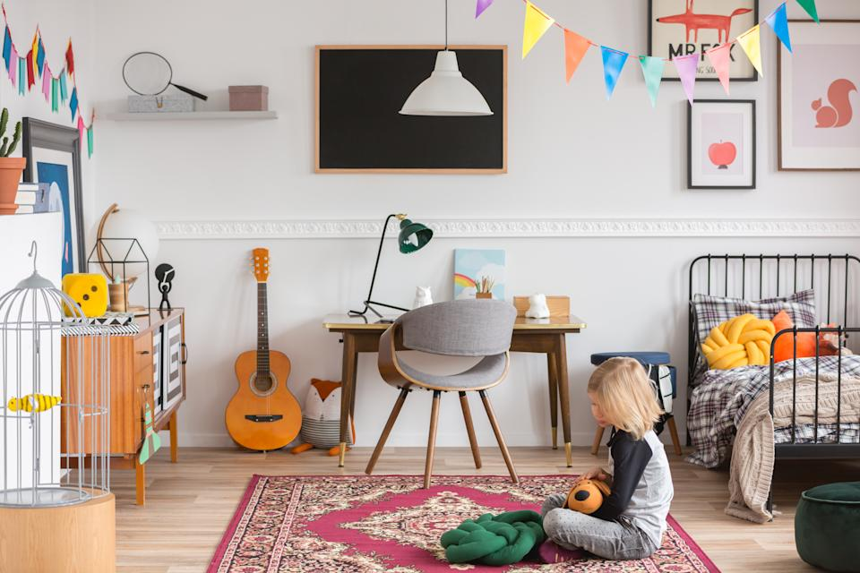 Little kid sitting on the rug in the white bedroom with vintage furniture