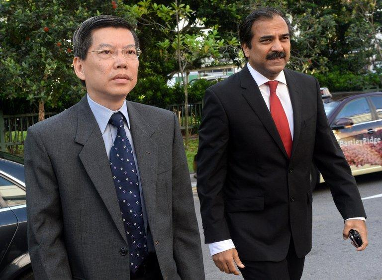 Former top civil servant Peter Lim (L) arrives with his lawyer at the Subordinate courts in Singapore, on June 13, 2013. Lim was jailed for six months for receiving oral sex from a female executive of a supplier company in return for business favours