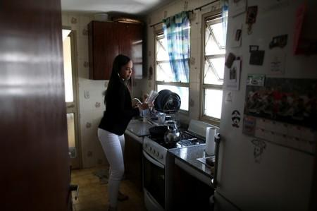 Nunes grabs a glass in her kitchen in Buenos Aires