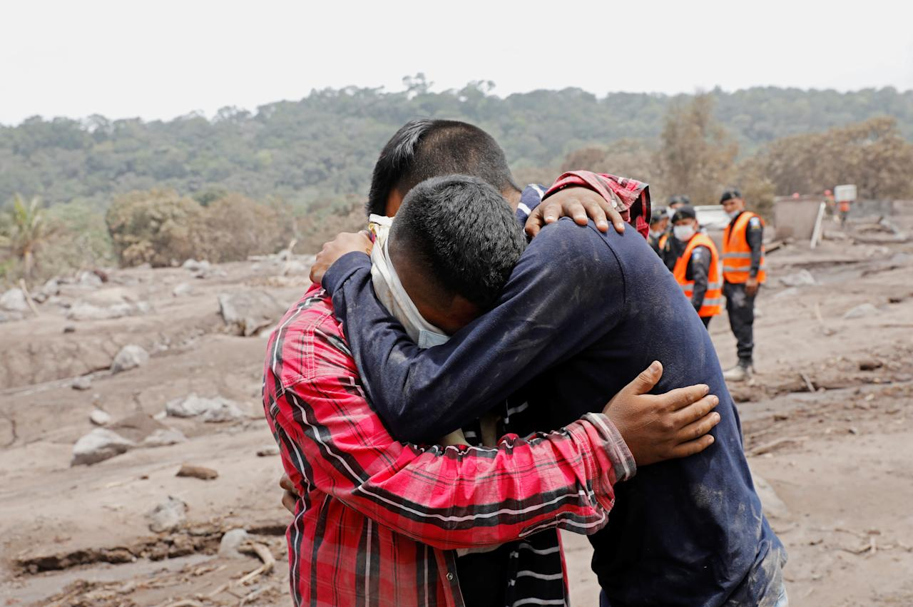 <p>Brian Rivera, who lost 13 members of his family during the eruption of the Fuego volcano, is comforted, near debris of his home at San Miguel Los Lotes, Escuintla, Guatemala, June 7, 2018. (Photo: Carlos Jasso/Reuters) </p>