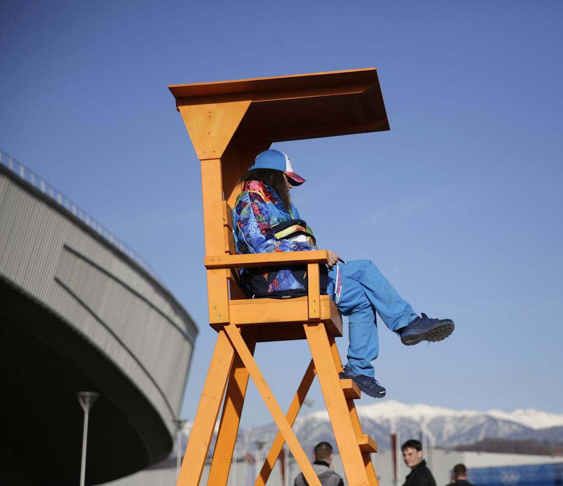 A security officer watches the crowd from an elevated position outside the Adler Arena Skating Center during the 2014 Winter Olympics in Sochi, Russia, Thursday, Feb. 13, 2014.(AP Photo/Matt Dunham)