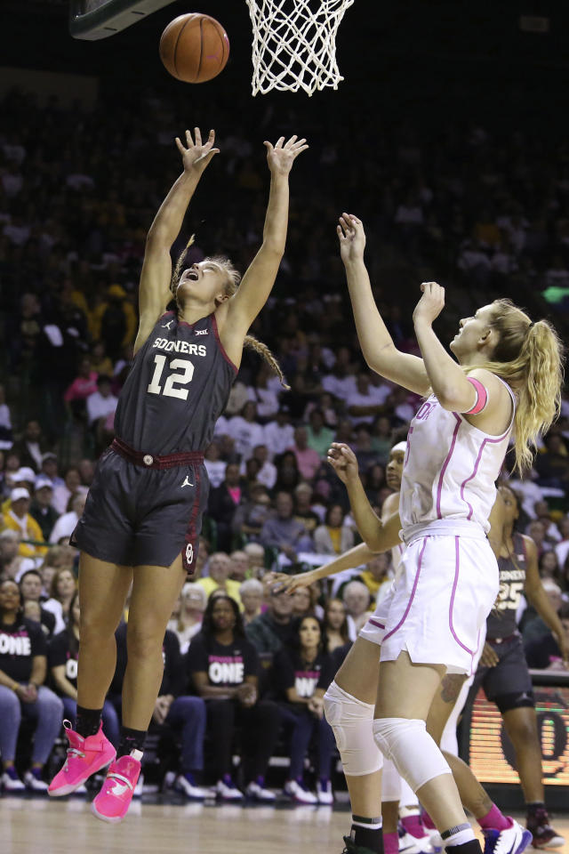 Oklahoma guard Gabby Gregory (12) scores past Baylor forward Lauren Cox (15) in the first half of an NCAA college basketball game Saturday, Feb. 22, 2020, in Waco, Texas. (AP Photo/Jerry Larson)