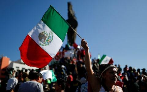 Demonstrators waving Mexican flags, attend to a protest against migrants in Tijuana - Credit: CARLOS GARCIA RAWLINS/REUTERS