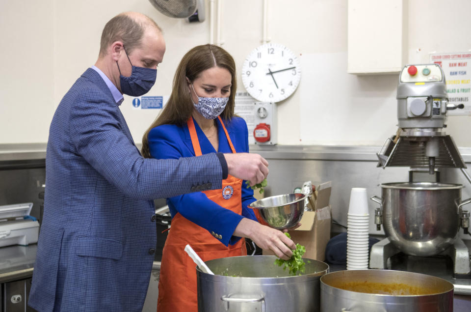 Britain's Prince William, Duke of Cambridge (L) and Britain's Catherine, Duchess of Cambridge, wear protective face coverings to combat the spread of the coronavirus, as they help prepare meals with representatives of Sikh Sanjog, a Sikh community group, in the cafe kitchen at the Palace of Holyroodhouse, in Edinburgh on May 24, 2021, during the Duke's week-long visit to Scotland. - During the visit the Duke and Duchess meet representatives of a Sikh community group to hear about their work. (Photo by Jane Barlow / POOL / AFP) (Photo by JANE BARLOW/POOL/AFP via Getty Images)