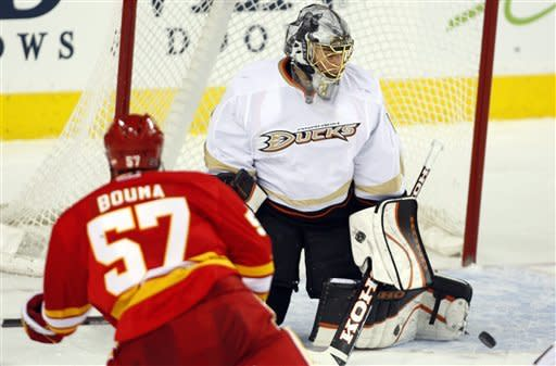 Anaheim Ducks goalie Jonas Hiller, right, from the Czech Republic, kicks the puck away on a shot from Calgary Flames' Lance Bouma during second period NHL hockey action in Calgary, Alberta, Saturday, April 7, 2012. (AP Photo/The Canadian Press, Jeff McIntosh)