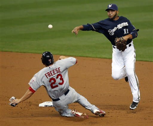 Milwaukee Brewers' Alex Gonzalez (11) forces out St. Louis Cardinals' David Freese (23) and throws to first base to complete a double play on Cardinals' Yadier Molina during the second inning of a baseball game, Saturday, April 7, 2012, in Milwaukee. (AP Photo/Jeffrey Phelps)