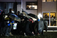 People in a residential building watch as demonstrators gather Tuesday, April 13, 2021, near the Brooklyn Center (Minn.) Police Department to protest Sunday's fatal shooting of Daunte Wright during a traffic stop. (AP Photo/John Minchillo)