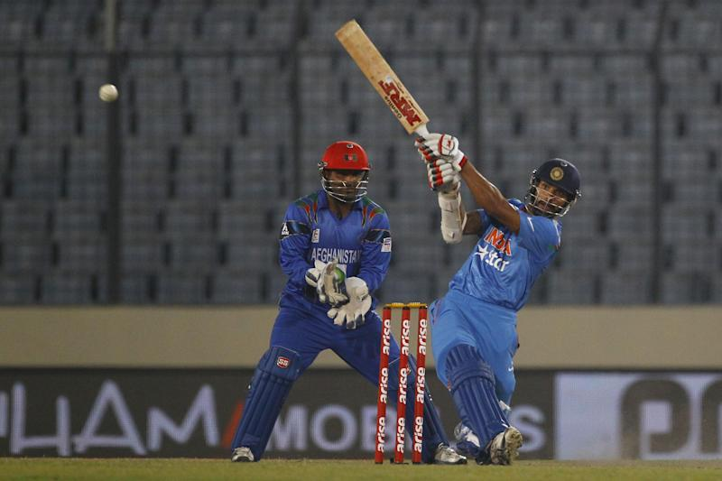 India's Shikhar Dhawan, right, plays a shot as Afghanistan's Mohammad Shahzad watches during their Asia Cup one-day international cricket match in Dhaka, Bangladesh, Wednesday March 5, 2014. (AP Photo/A.M. Ahad)