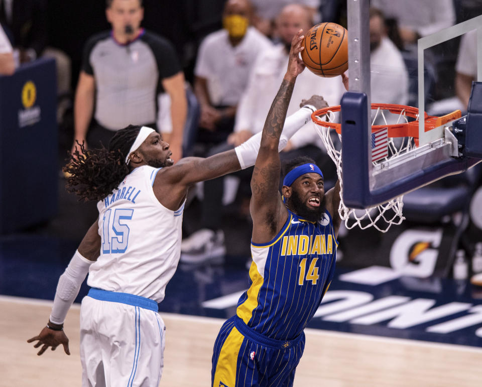 Indiana Pacers forward JaKarr Sampson (14) scores while Los Angeles Lakers center Montrezl Harrell (15) defends during the second half of an NBA basketball game in Indianapolis, Saturday, May 15, 2021. (AP Photo/Doug McSchooler)