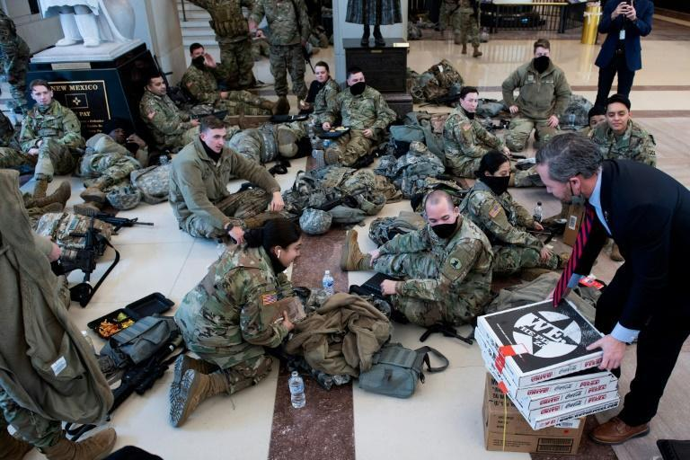 Members of the National Guard receive food in the Capitol Visitors Center on January 13, 2021 ahead of the House vote impeaching US President Donald Trump