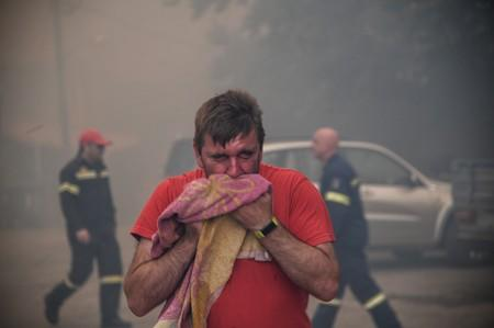 A man reacts to smoke as a wildfire burns at the village of Kontodespoti, on the island of Evia