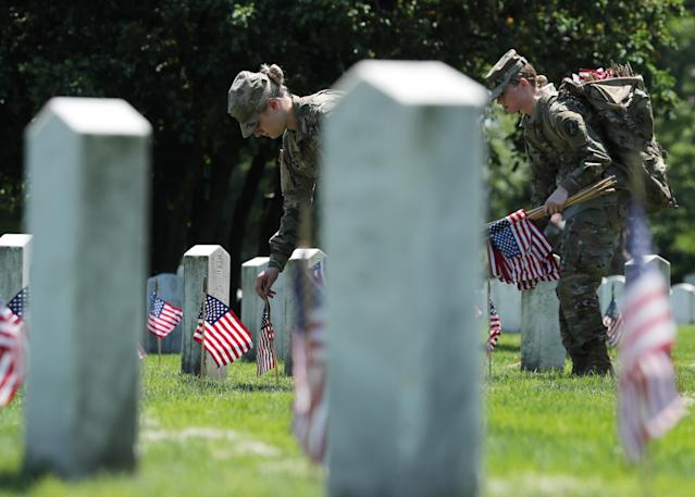 <p>U.S. Army soldiers of the 3rd United States Infantry Regiment place U.S. flags on graves at Arlington National Cemetery in advance of Memorial Day in Arlington, Va., May 24, 2018. (Photo: Jonathan Ernst/Reuters) </p>